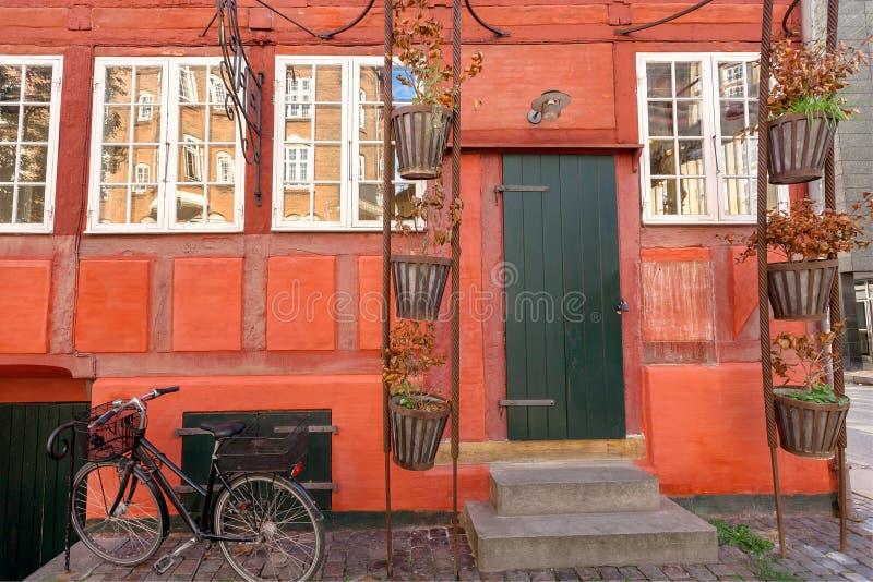 Красный цвет огораживает дом традиционного стиля в Копенгагене, Дании Фасад исторического корабля кирпичного здания и велосипеда стоковая фотография rf