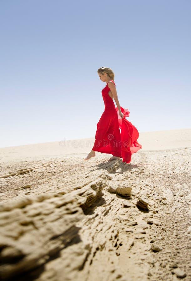 Красный цвет одел красивую тонкую женщину, прогулки в пустыне стоковые изображения