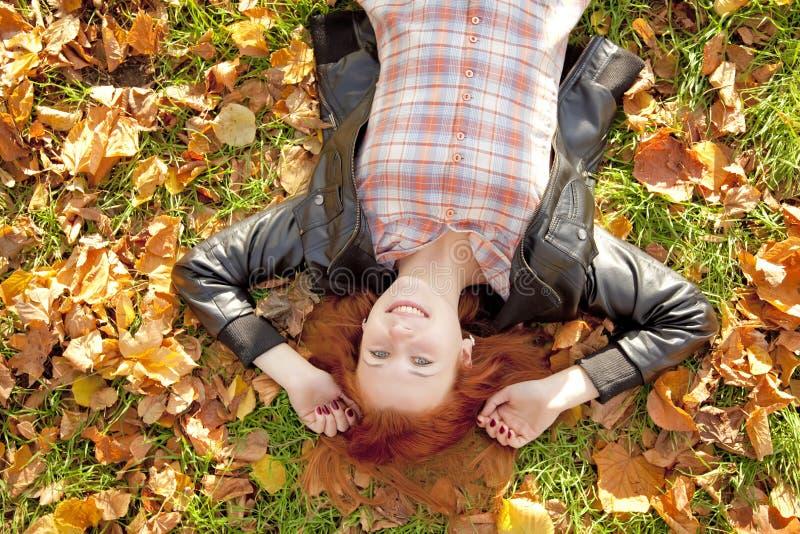 красный цвет парка девушки осени с волосами счастливый стоковая фотография
