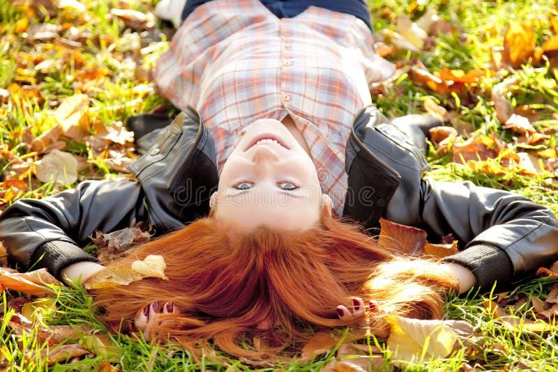красный цвет парка девушки осени с волосами счастливый стоковое изображение