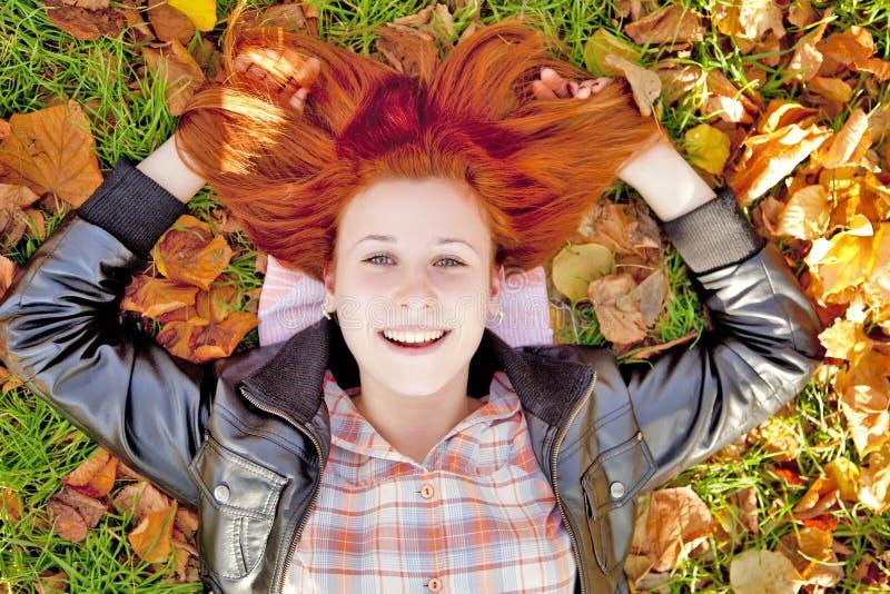 красный цвет парка девушки осени с волосами счастливый стоковое фото rf