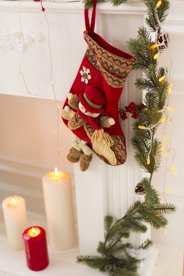 Красный цвет рождества или Нового Года связал чулок с снеговиком, горящими свечами, декоративные ветви мех-дерева и электрический стоковое фото rf