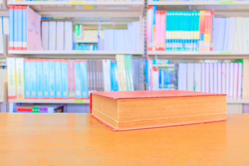 красный цвет старой книги в школьной библиотеке на деревянном столе расплывчатая предпосылка книжных полок стоковое фото