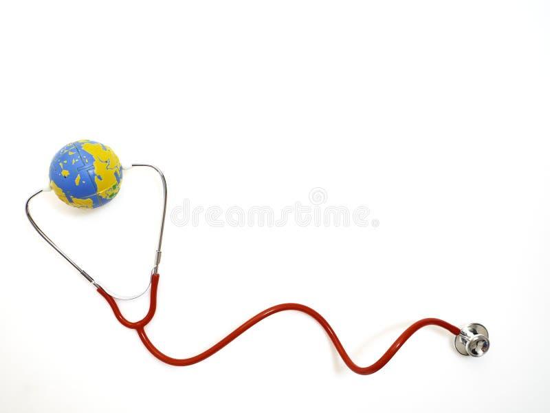 Красный цвет стетоскопа с глобусом на белой предпосылке стоковое фото