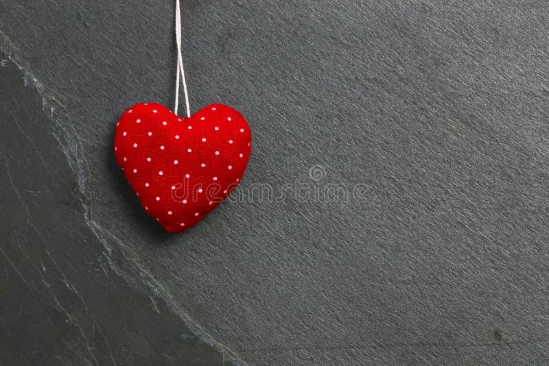 Красный цвет с белыми точками любит смертную казнь через повешение сердца валентинки на сером шифере стоковое фото