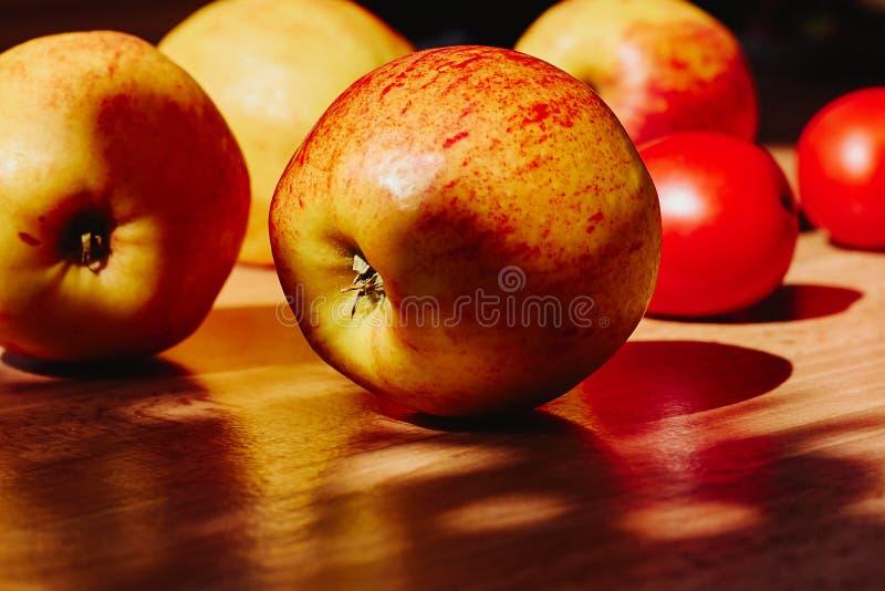Красный цвет с желтыми яблоками и томатами на деревянной предпосылке стоковые изображения