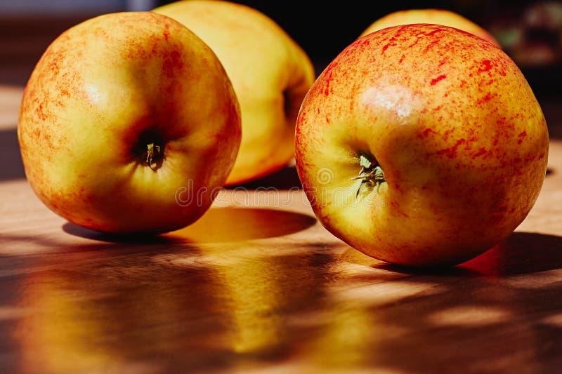 Красный цвет с желтыми яблоками на деревянной предпосылке стоковые фото