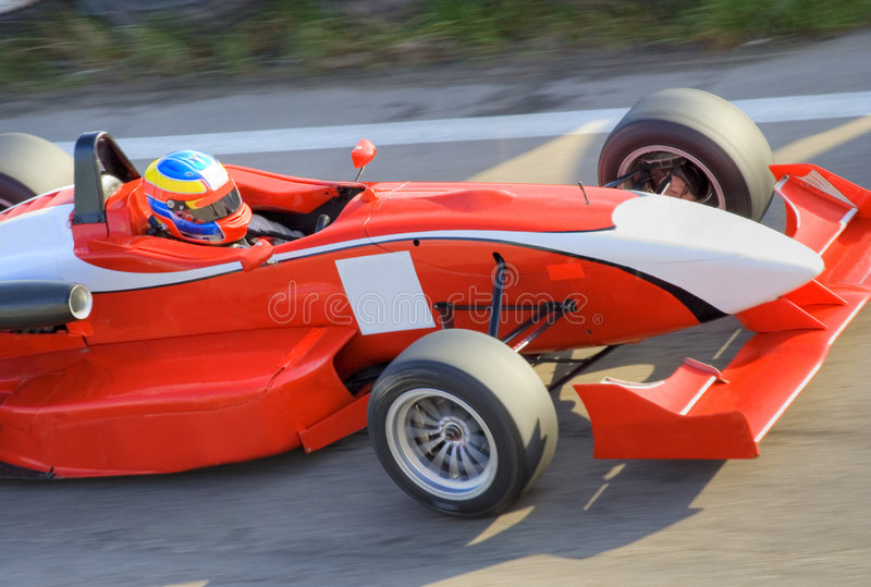 красный цвет формулы автомобиля участвуя в гонке стоковые фото