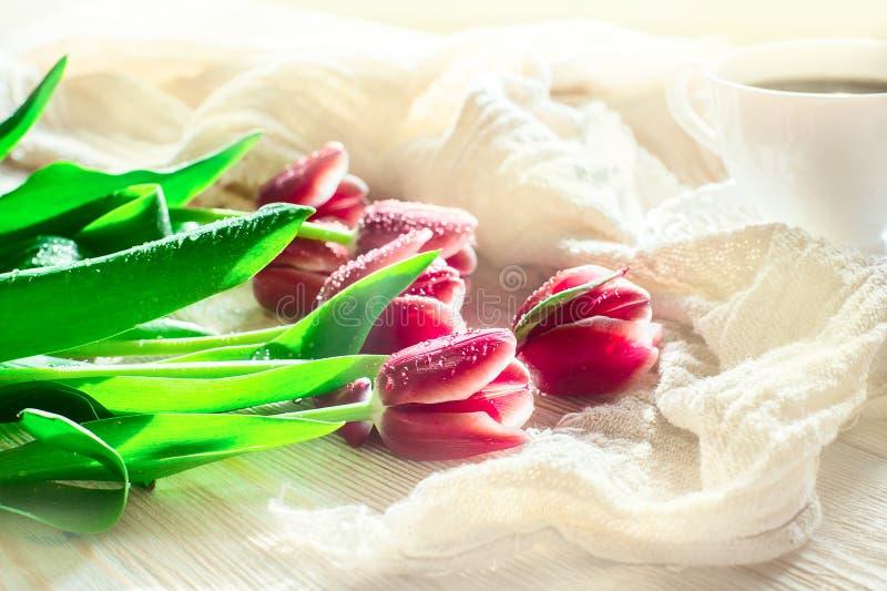 Красный цвет цветет тюльпаны и cuf кофе на светлом backgroung положите его светлый спать в постель утра человека стоковая фотография rf