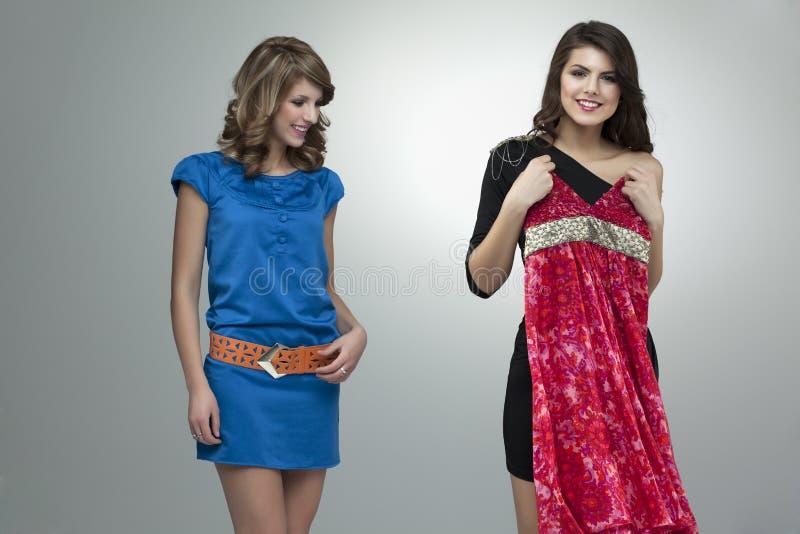 красный цвет цветка платья счастливый судя за 2 женщины стоковые фото