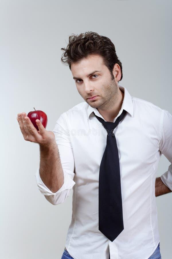 красный цвет человека удерживания яблока стоковое изображение rf