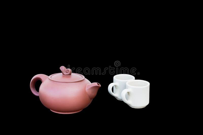 Красный чайник и белые чашка изолированные на черной предпосылке стоковое изображение