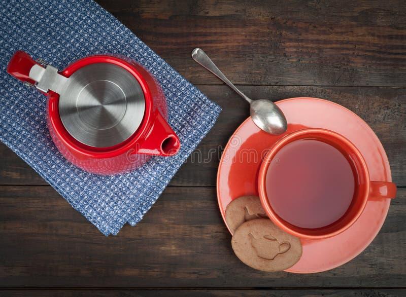 Красный чайник с оранжевыми чашка и поддонником и печеньями стоковые фотографии rf
