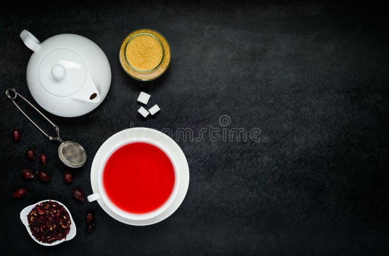 Красный чай с высушенными плодоовощами и чайником на космосе экземпляра стоковое фото
