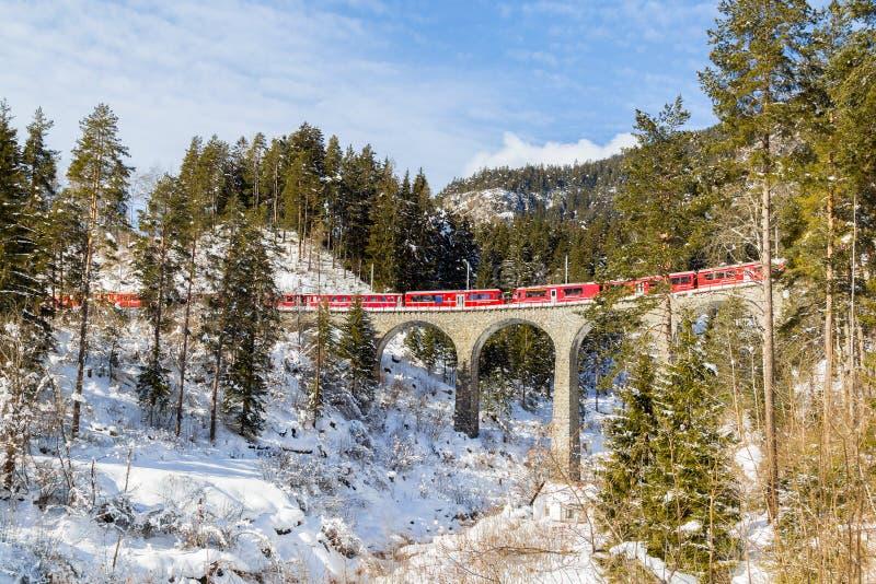 Красный швейцарский поезд проходя на виадук Schmitten, стоковое изображение
