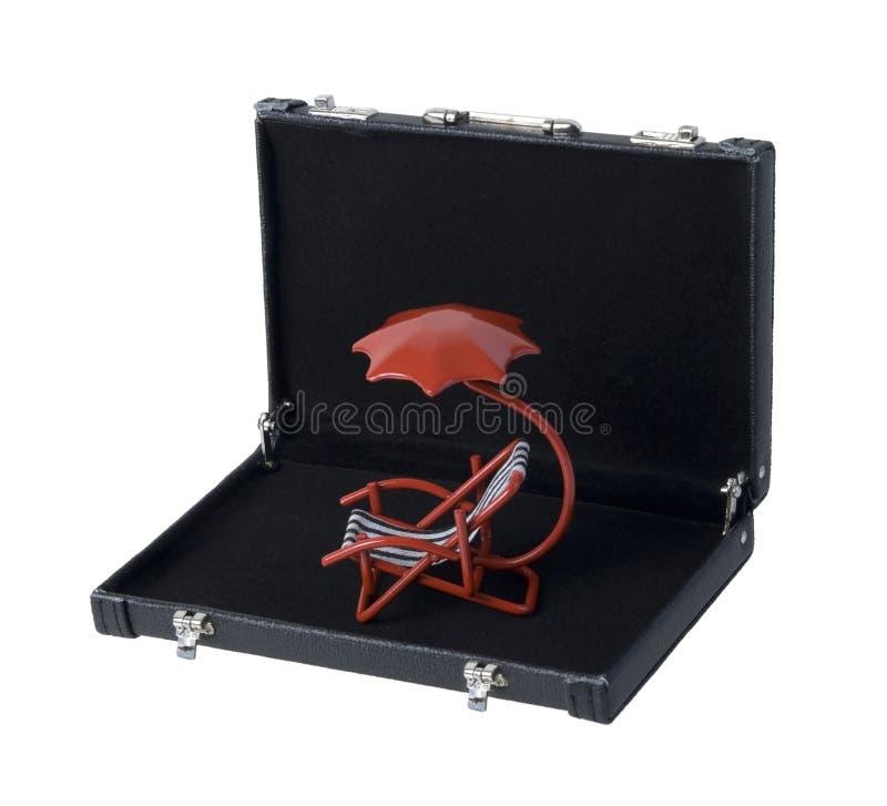 Красный шезлонг с зонтиком в портфеле стоковое фото
