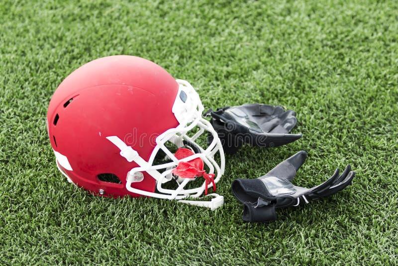 Красный шлем футбола с задними перчатками на поле стоковая фотография