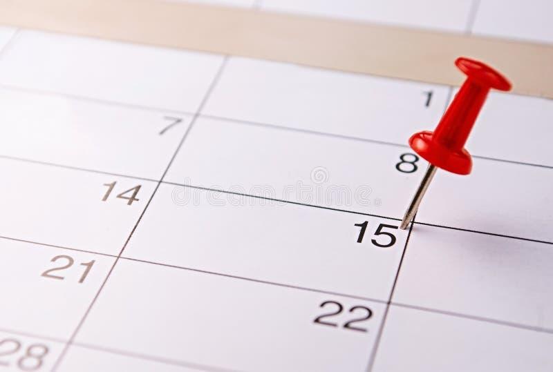 Красный штырь отмечать пятнадцатое на календаре стоковая фотография rf