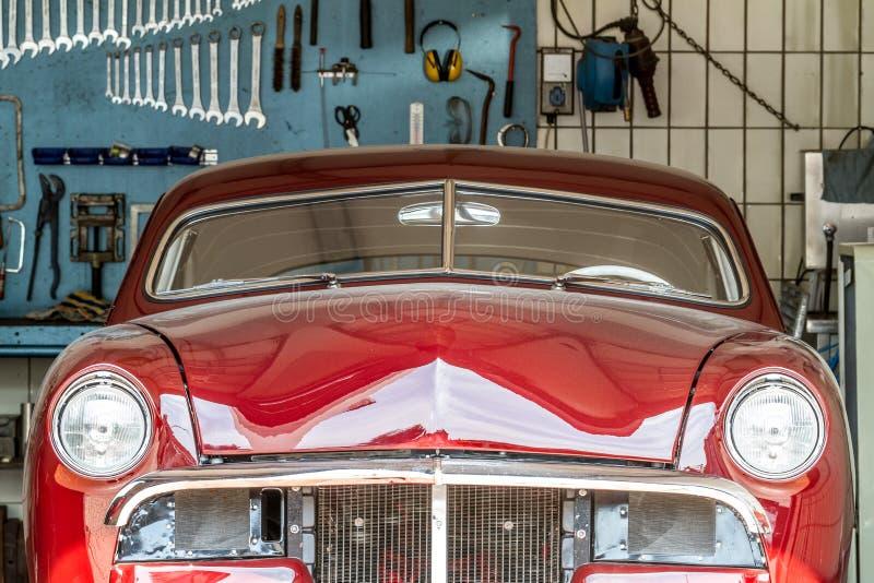 Красный oldtimer в ремонтной мастерской автомобиля в процессе стоковое фото