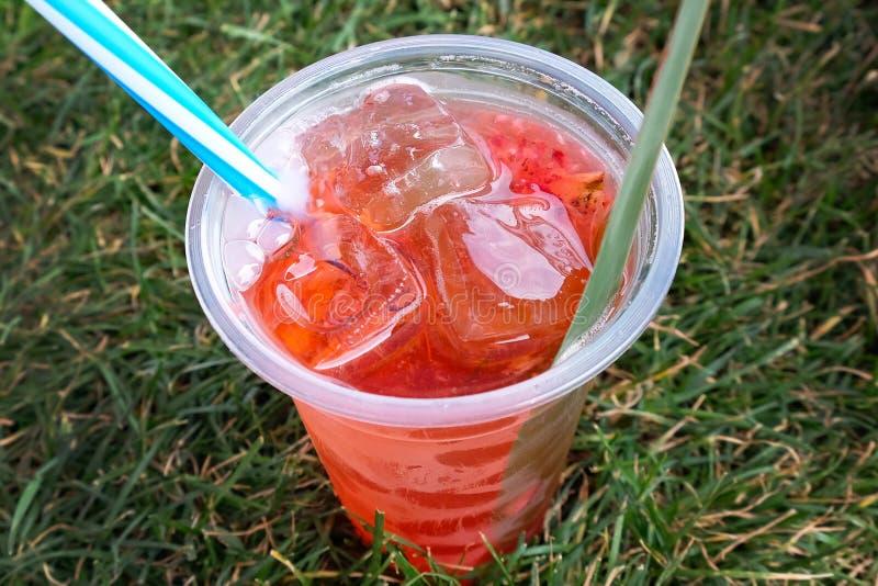 Красный sangria с льдом в пластиковом стекле с соломой на траве стоковое фото