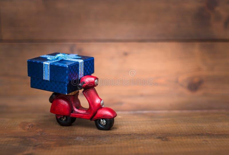 Красный vespa мотоцикла транспортирует голубую подарочную коробку стоковые фото