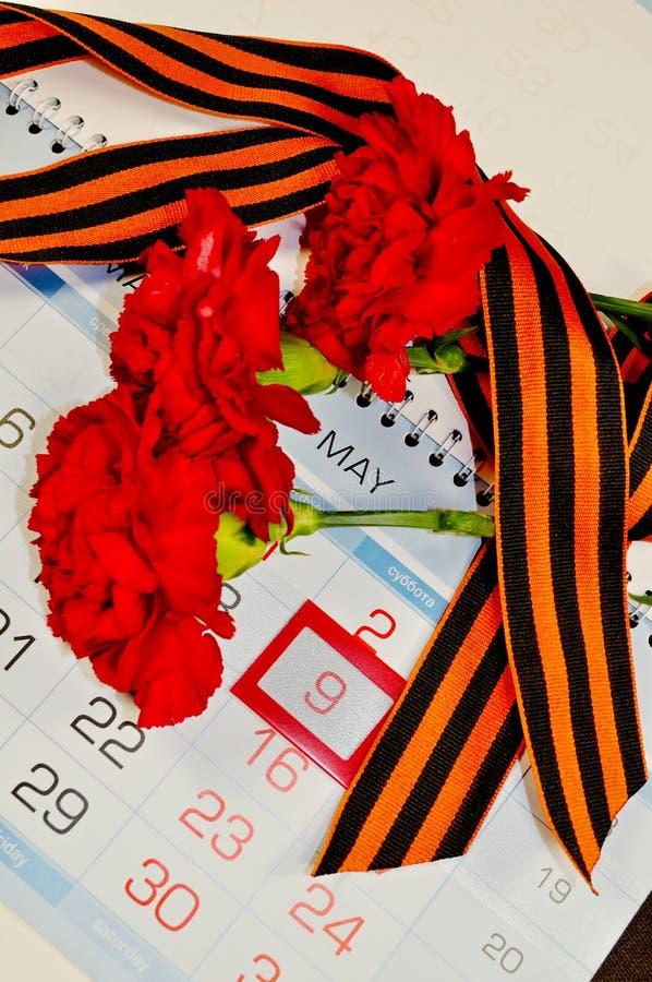 3 красных гвоздики обернутой с лентой Джордж на календаре с 9-ое мая датируют - натюрморт дня победы стоковые изображения
