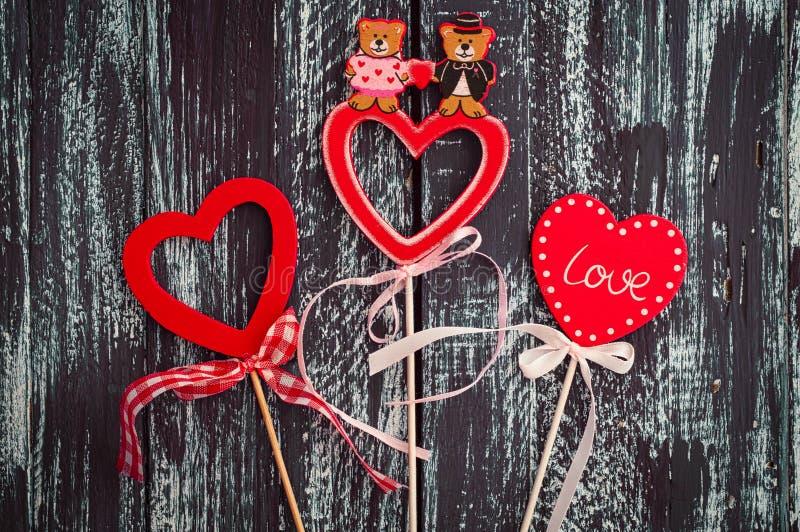 3 красных деревянных сердца на черное поверхностное красочном иллюстрация штока