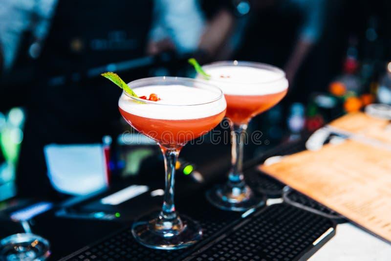 2 красных красочных коктеиля, который служат в ночном клубе стоковые фотографии rf