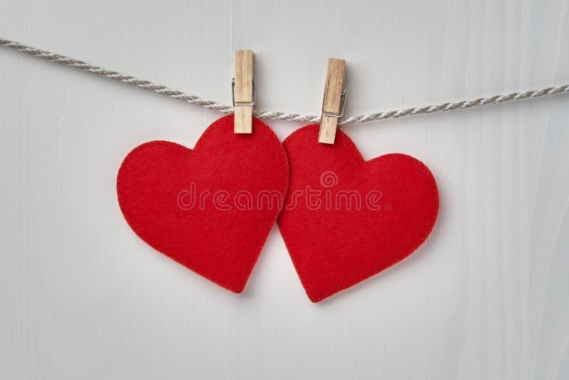 2 красных сердца Валентайн вися от веревочки зафиксированной зажимками для белья на белой деревянной предпосылке стоковое изображение
