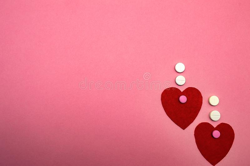 2 красных сердца на розовой предпосылке с любовью медицины таблеток стоковое изображение