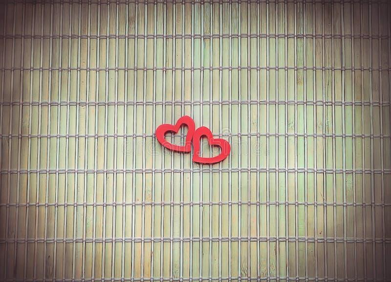 2 красных сердца на бамбуковой салфетке стоковая фотография rf