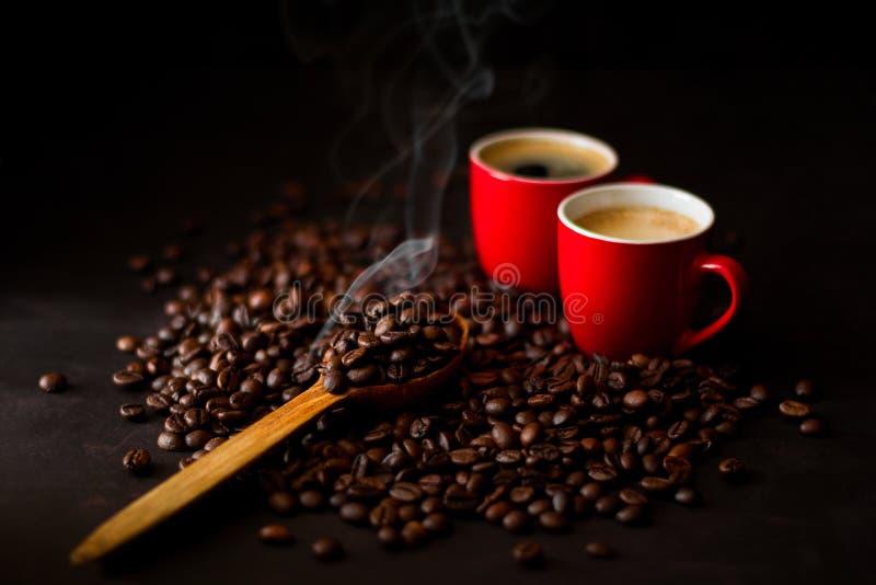 2 красных чашки эспрессо с кофейными зернами на темном деревянном backgr стоковая фотография