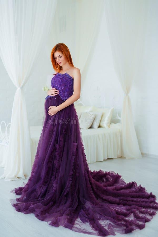 Красота беременности Красивая элегантная беременная женщина readhead в фиолетовом платье представляя в нежном домашнем интерьере стоковое изображение