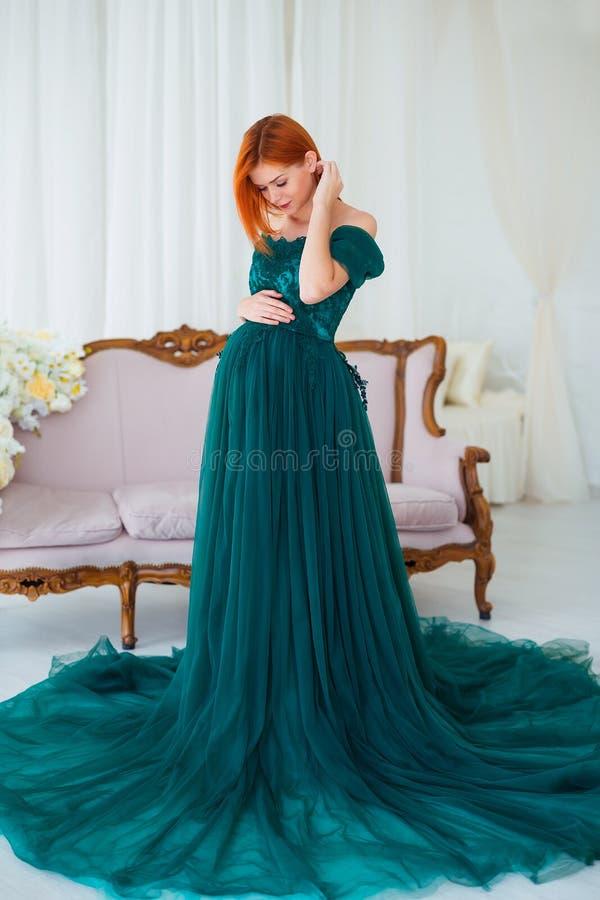 Красота беременности Красивая элегантная беременная женщина readhead в зеленом платье представляя в нежном домашнем интерьере стоковое изображение
