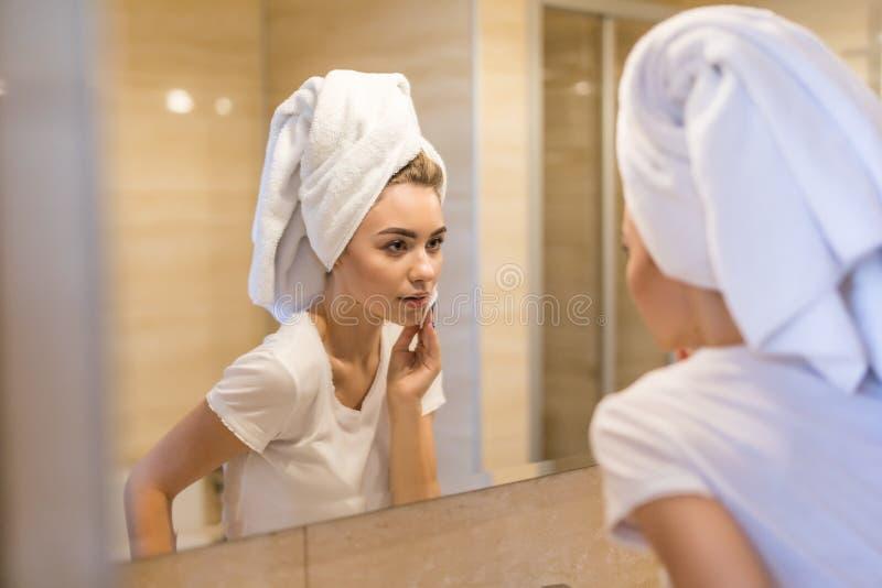 Красота, забота кожи и концепция людей Усмехаясь молодая женщина моя ее сторону с лицевой очищая губкой на bathroom стоковые изображения rf
