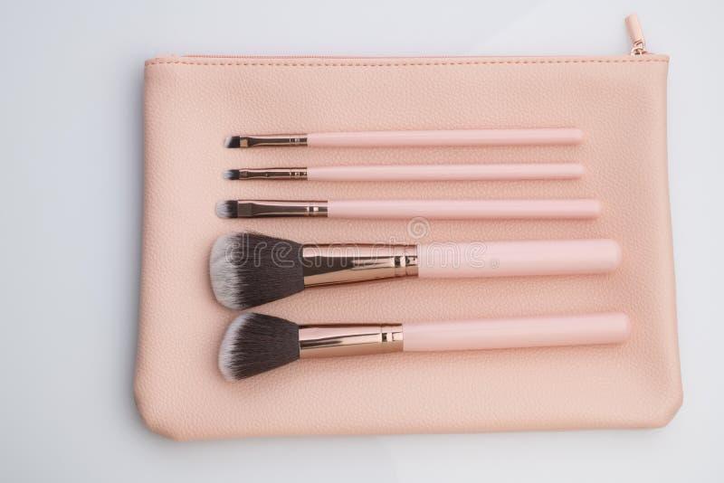 Красота и мода: Набор щеток макияжа с розовым кожаным мешком снятым в студии над белой предпосылкой стоковая фотография