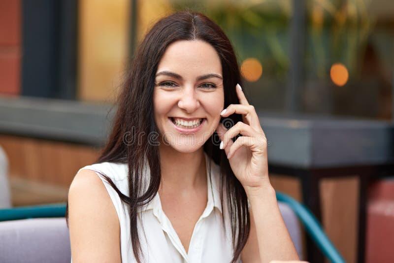 Красота, отдых и положительная концепция эмоций Счастливая молодая женщина брюнета с зубастой улыбкой, одетой в белой блузке лета стоковые изображения rf