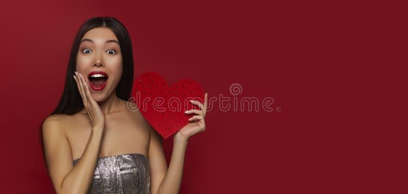 Красота удивила молодую девушку фотомодели с большим сердцем Валентайн в руках Любовь Торжество Символ дня Валентайн скопируйте к стоковая фотография