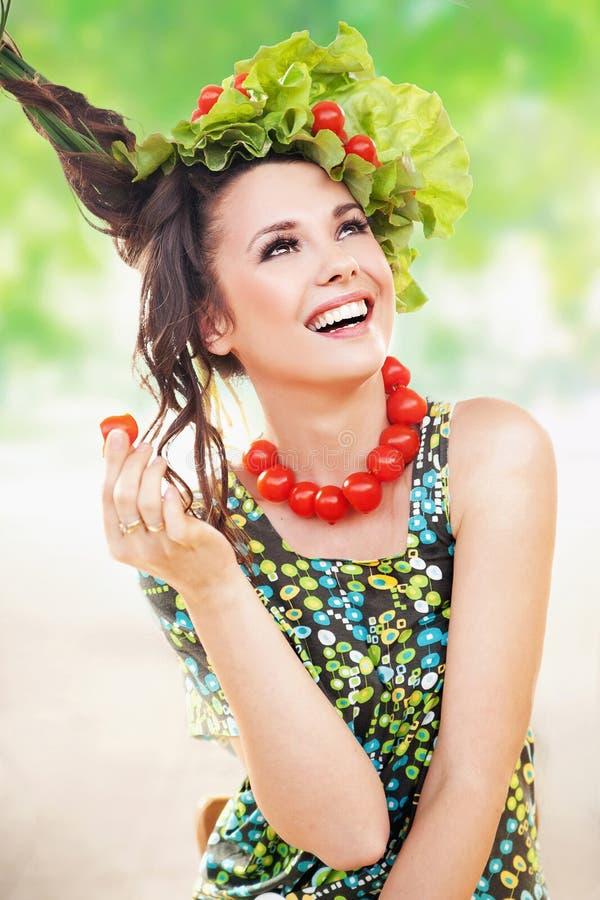 Красотка брюнет представляя с томатом стоковое изображение rf