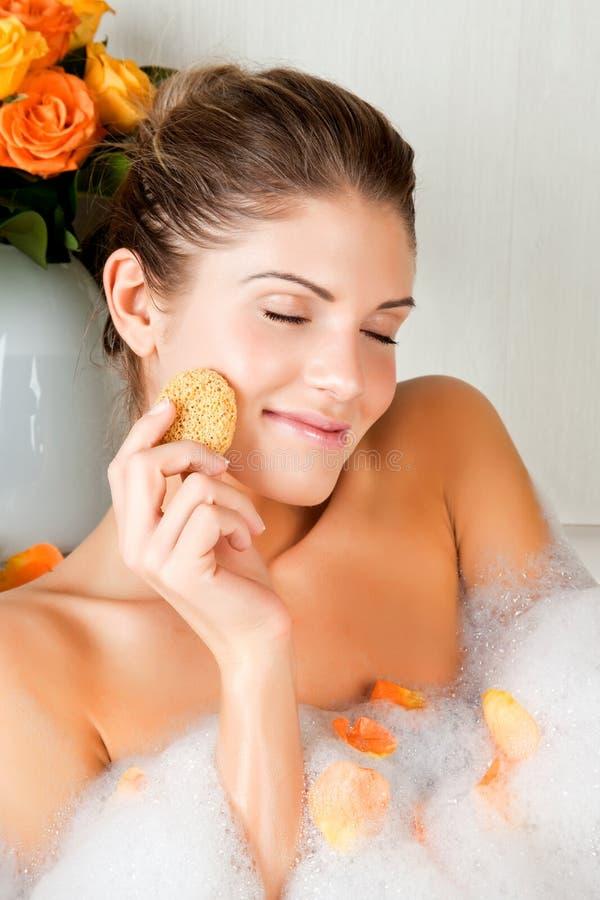 красотка ванны смотрит на ее моя детенышей женщины стоковое изображение rf