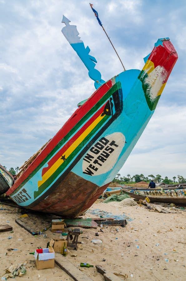 Красочная африканская пирога или деревянная шлюпка будучи покрашенным на пляже стоковое фото rf