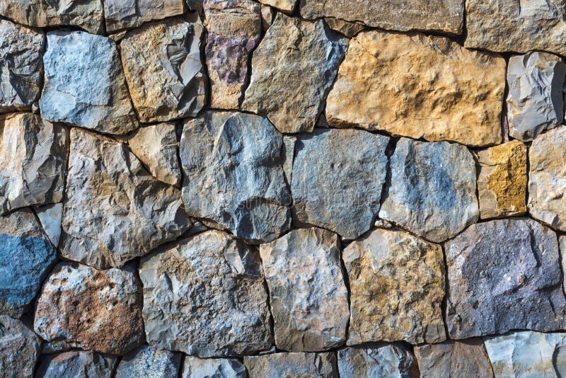 Красочная естественная предпосылка каменной стены с скачками голубыми и оранжевыми камнями стоковое фото
