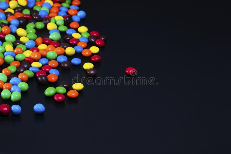 Красочная конфета разлитая на черной таблице стоковые изображения