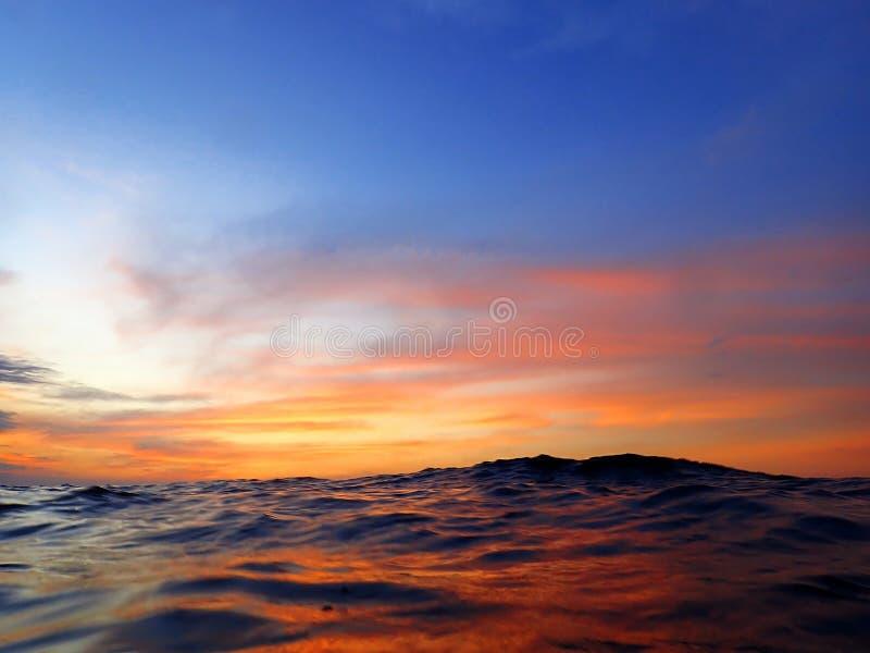 Красочная поверхность с яркими цветами отражения захода солнца и ночи перед начинать пикирования ночи стоковая фотография