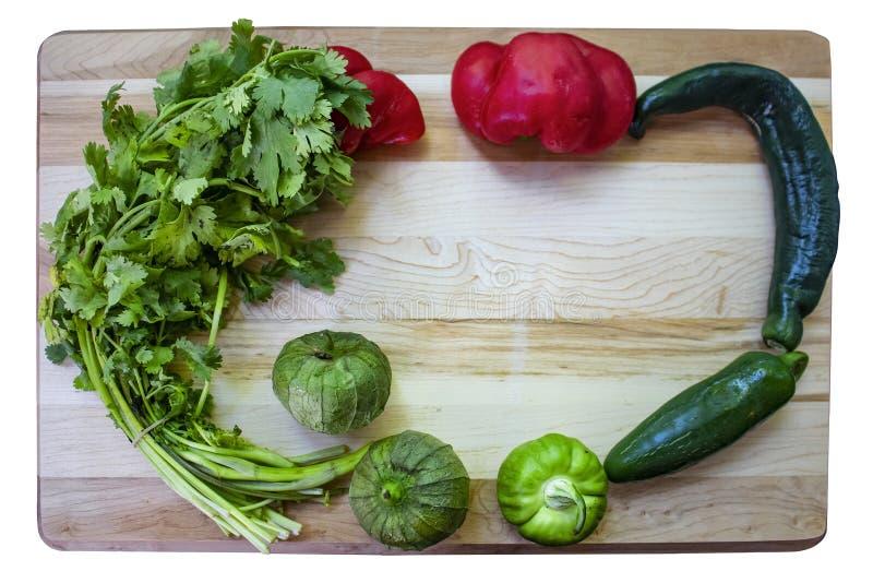 Красочная рамка сальсы - разделочная доска с cilantro и tomatillos и сортированные горячие и сладостные перцы аранжировали вокруг стоковое фото rf