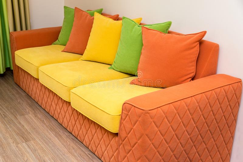 Красочная софа желт-апельсина с зелеными, желтыми и оранжевыми подушками стоковое изображение rf