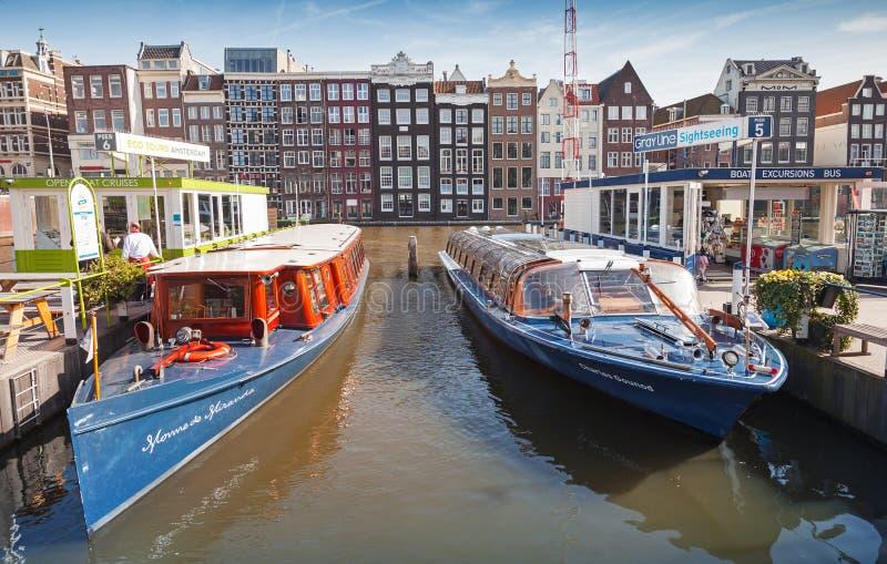 Красочная стойка прогулочных катеров причаленная на канале Damrak стоковые изображения rf