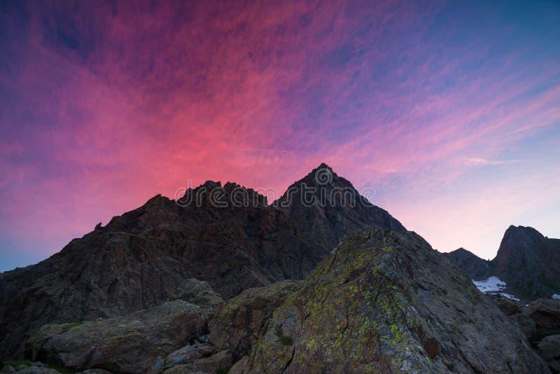 Красочное небо за скалистым горным пиком на итальянских Альпах на сумраке стоковые фото