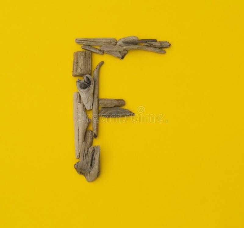 Красочное ` f ` письма сделанное из деревянных ручек на желтой предпосылке стоковые фото