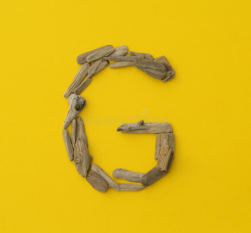 Красочное ` g ` письма сделанное из деревянных ручек на желтой предпосылке стоковое фото rf